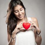 Woman looking at a small plastic heart self-esteem