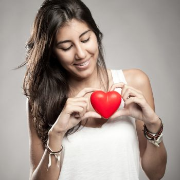 Woman looking at a small plastic heart self-esteem