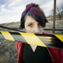 3011823 - punk girl outdoors behind a strip of yellow and black caution tape